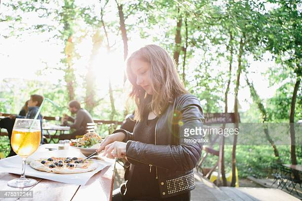 young woman cuts her pizza in beer garden