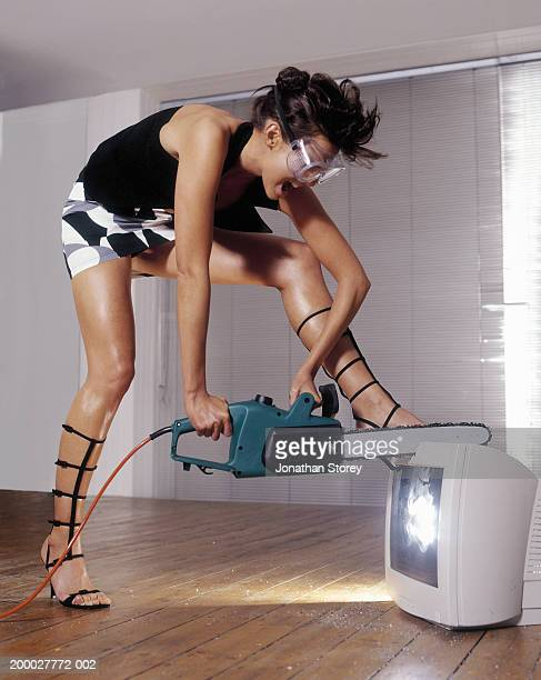 Young woman cutting computer monitor with electric saw