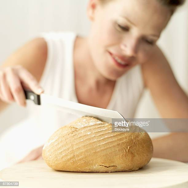 Young woman cutting doughnut with knife