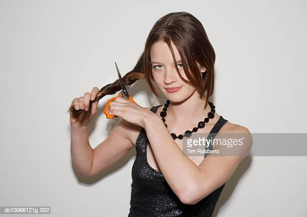 Young woman cutting hair, smiling, portrait