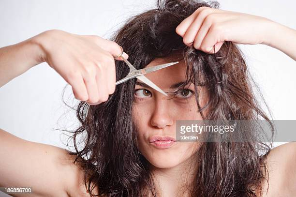 A young woman cutting her own hair
