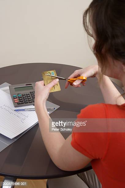 Young woman cutting up credit card, view over woman's shoulder