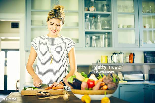 Young woman cutting vegetables at kitchen island