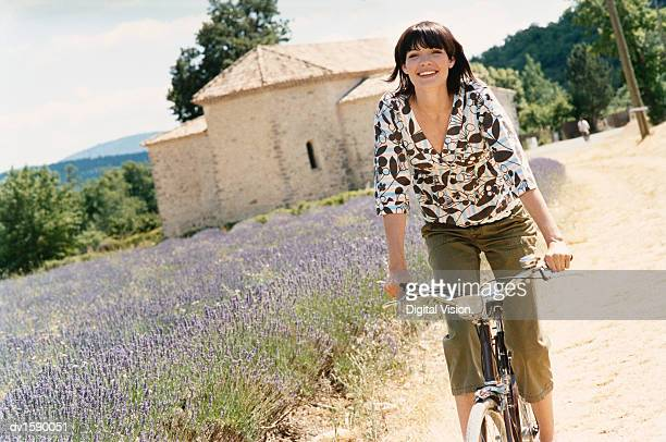 Young Woman Cycles on a Path by a Lavender Field in Provence, France
