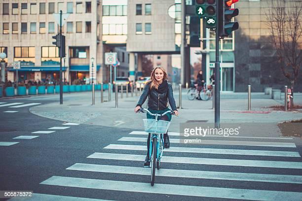 Junge Frau Fahrradfahren und überqueren Sie die Straße
