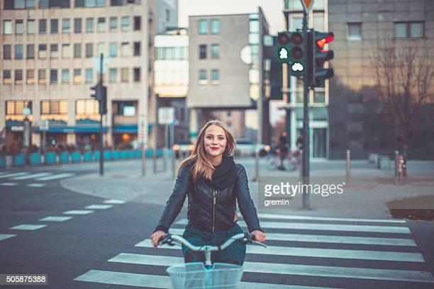 Giovane donna in bicicletta, attraversando la strada
