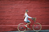 Young woman in blue dress rides a red vintage bike with basket in the streets of Moscow.