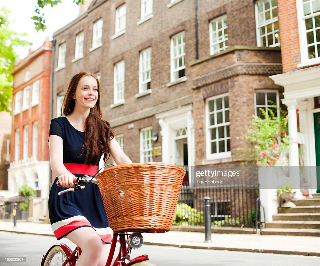 Young woman cycling outside houses : Stock Photo
