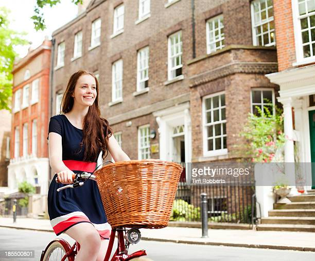 Young woman cycling outside houses