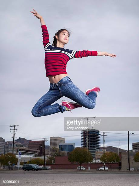 Young woman dancer leaping over cityscape