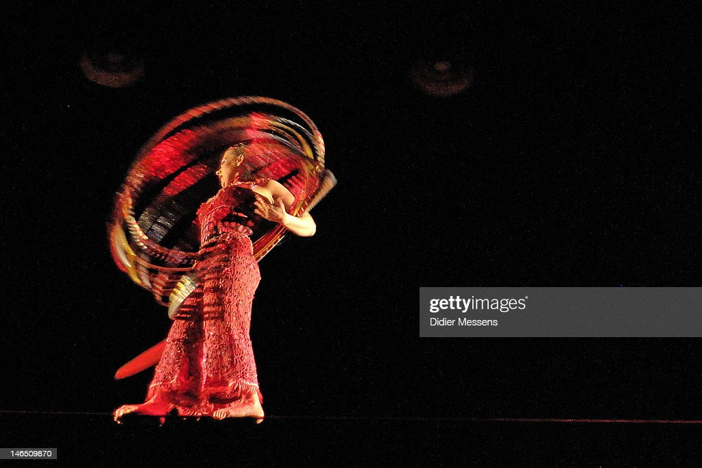 A young woman dances six meters above the ground across a tight-wire using point shoes, a unicycle, multiple hoops, and her bare feet during the Belgian premiere of the Cirque du Soleil show Corteo on June 13, 2012 in Antwerpen, Belgium.