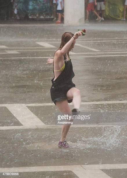 A young woman dances under torrential rain in Saint Mark's Square during a thunderstom that hit the city this afternoon on July 8 2015 in Venice...