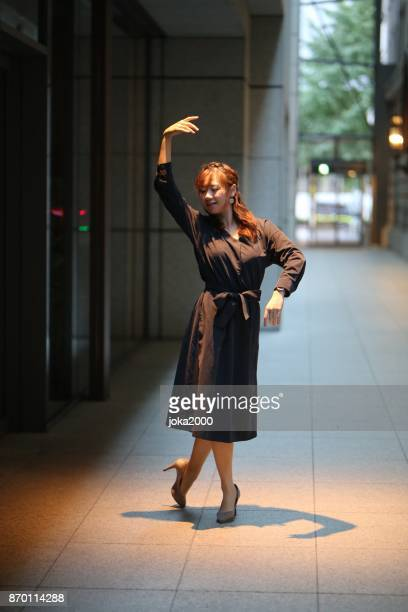 建物の間のパスで踊る若い女性