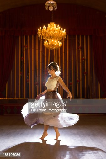 Young woman dancing barefoot in ballroom