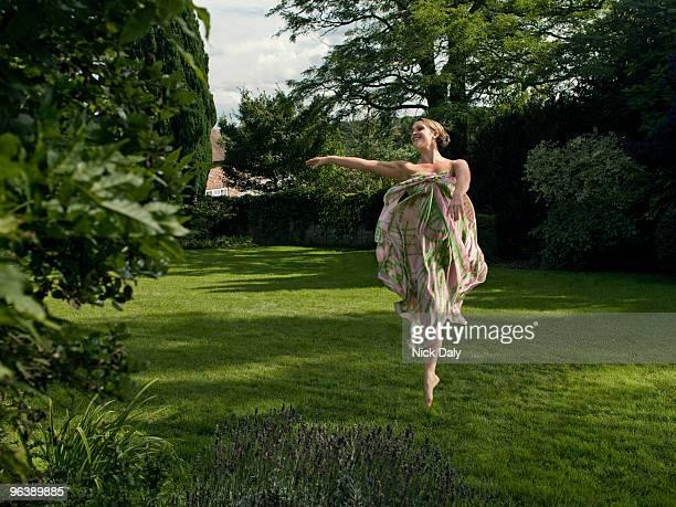 A young woman dancing in a garden