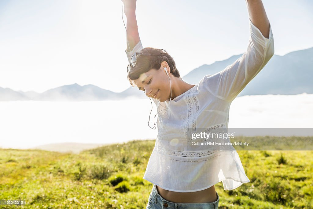 Young woman dancing in field, Tyrol, Austria : Stock Photo