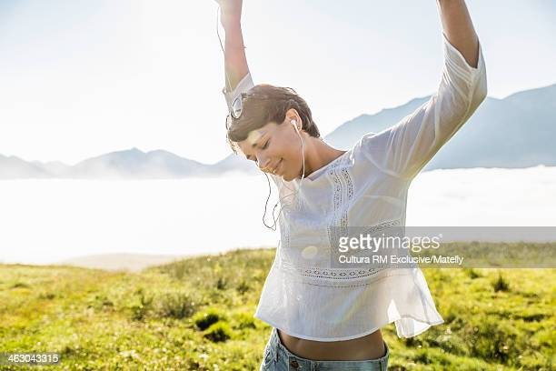 Young woman dancing in field, Tyrol, Austria