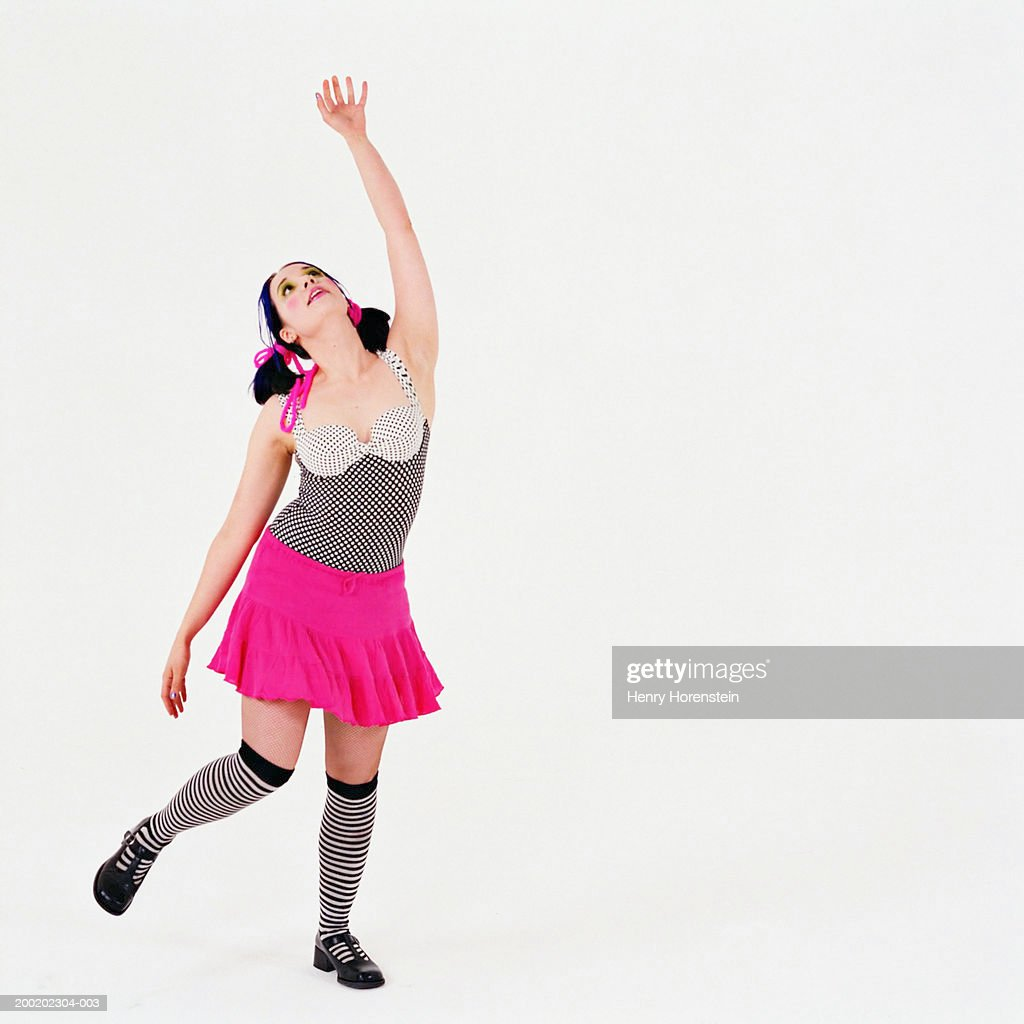Young woman dancing, looking up, arm raised : Stock Photo