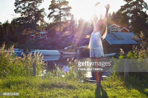 Young woman dancing next to lake, Gavle, Sweden