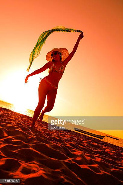 Young woman dancing on a tropical summer beach