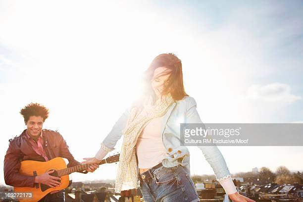 Young woman dancing on roof terrace, man playing guitar
