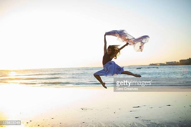 Young woman dancing on sunlit beach