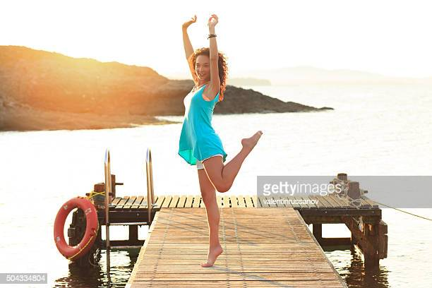 Young woman dancing on the pier