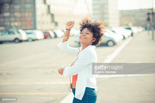 Young woman dancing to music on earphones in city