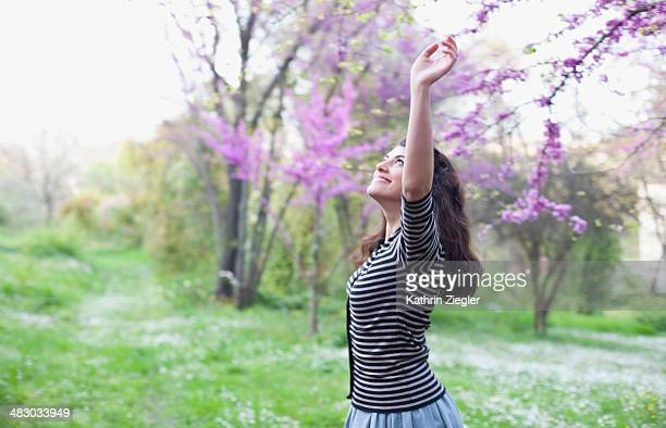 young woman dancing under blooming tree