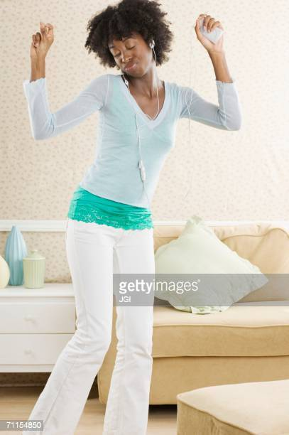Young woman dancing while listening to her headphones