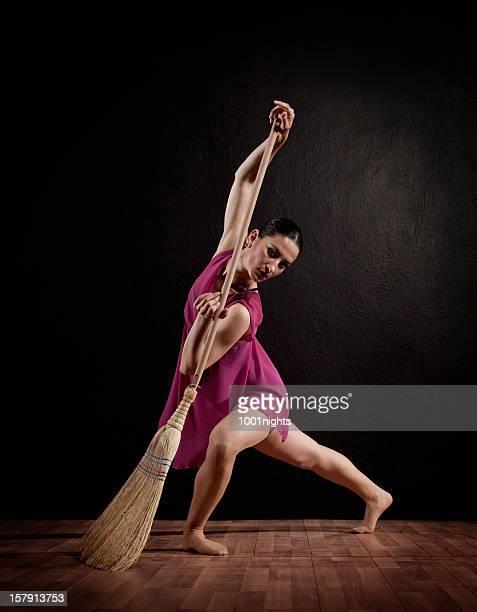 Jeune femme danse avec un balai