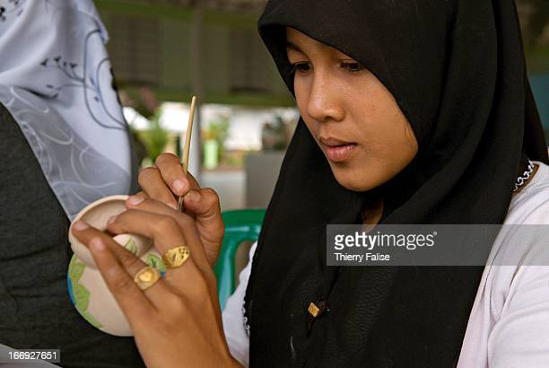 A young woman daughter of a widow at the Rotan Batu village paints a pot which will be sold to visitors and in the markets outside the village The...