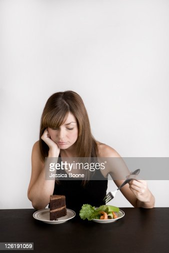 young woman deciding between cake and vegetables : Stock Photo