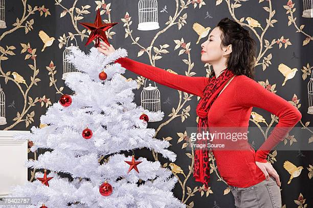 Young woman decorating christmas tree