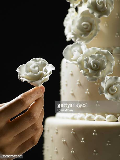 Young woman decorating layered cake with icing flowers
