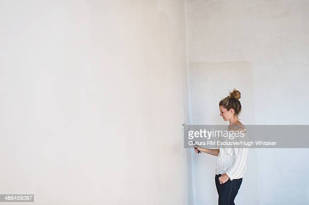 Young woman decorating with a paint roller at home