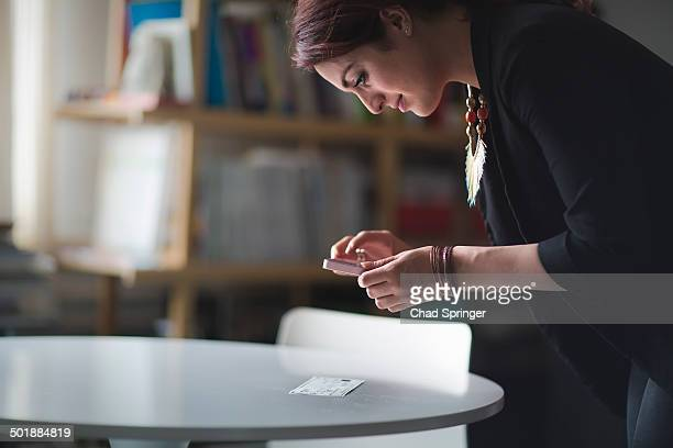 Young woman depositing cheque with smartphone