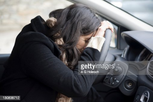 Young woman despairing at the wheel