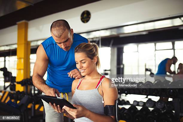 Young woman discussing workout plan with fitness instructor