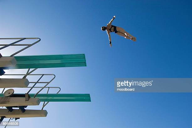 Young woman diving from diving board