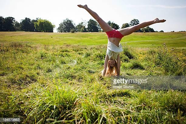 Junge Frau machen einen handstand in einem Feld