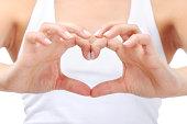 Young woman doing a heart shape