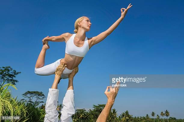 Jeune femme faisant yoga acrobatique avec un partenaire masculin