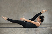 Young sporty woman practicing fitness, doing alternate leg stretch exercise, warm up pose, working out, wearing sportswear, black pants and top, indoor full length, against gray wall in sport studio
