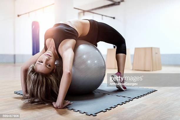 Young Woman Doing Backbend on Fitness Ball in Gym