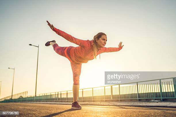 Young woman doing balance exercise at sunset.