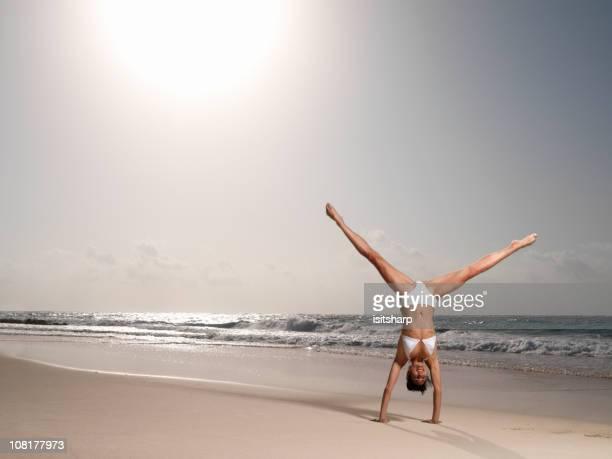 Young Woman Doing Cartwheel on Beach