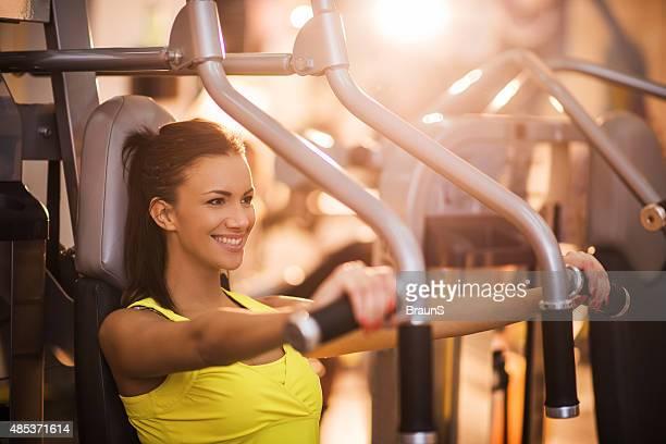 Junge Frau, die Brust-Übungen, die auf Übung Maschine im Fitnessstudio.