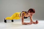 young woman doing elbow plank in studio