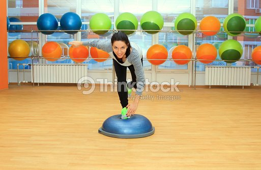 Young woman doing exercise on bosu ball : Stock Photo